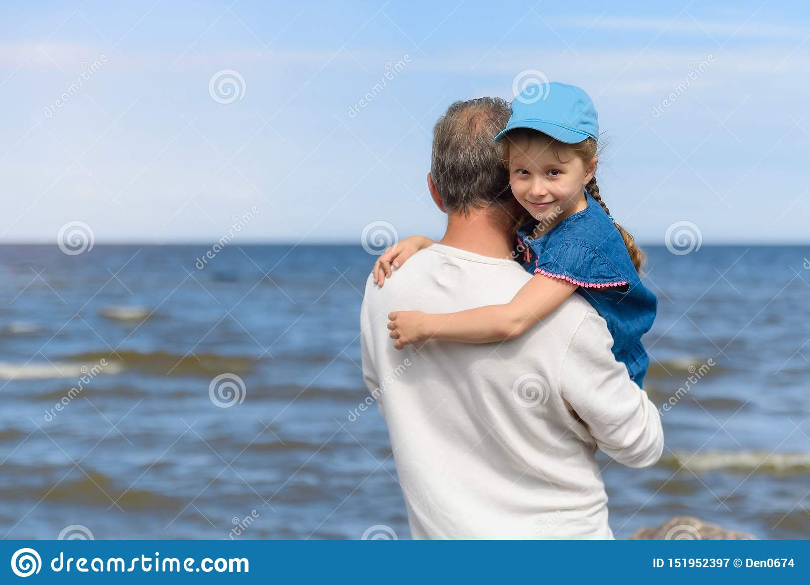 Happy father hugging his little daughter on the beach, father and daughter walking on the beach and posing to camera