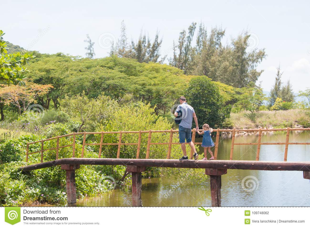 Happy father man with his little daughter walking across the wood sea bridge