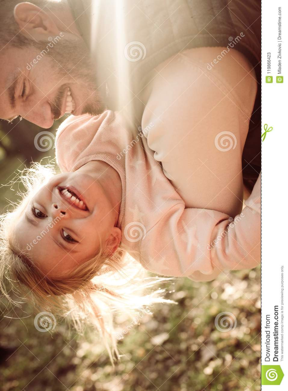 Happy father playing with daughter in park.