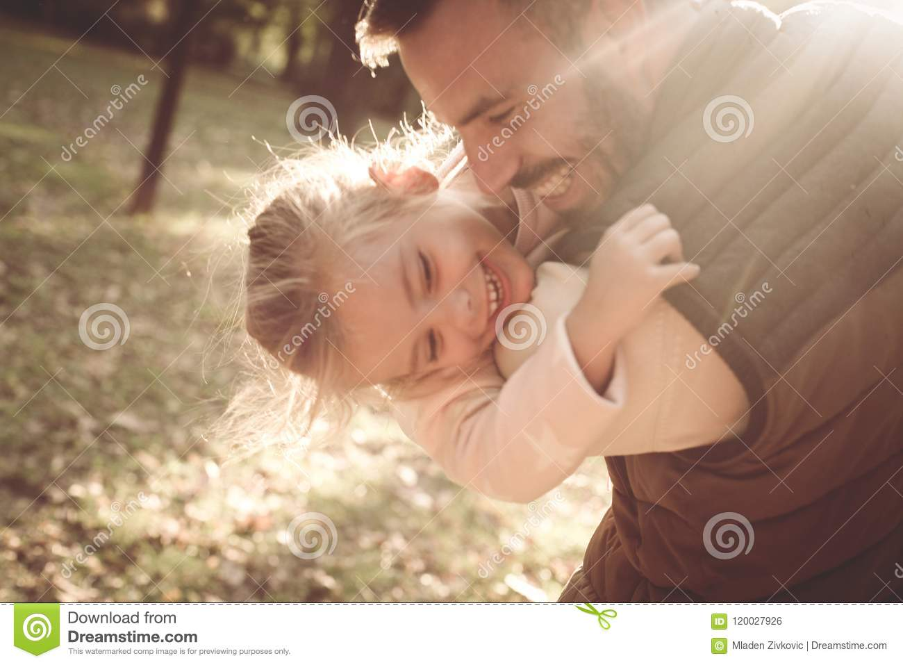 Happy father playing with daughter in park and hugging h