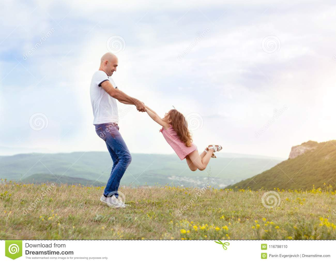 Father playing with his daughter in sunny field