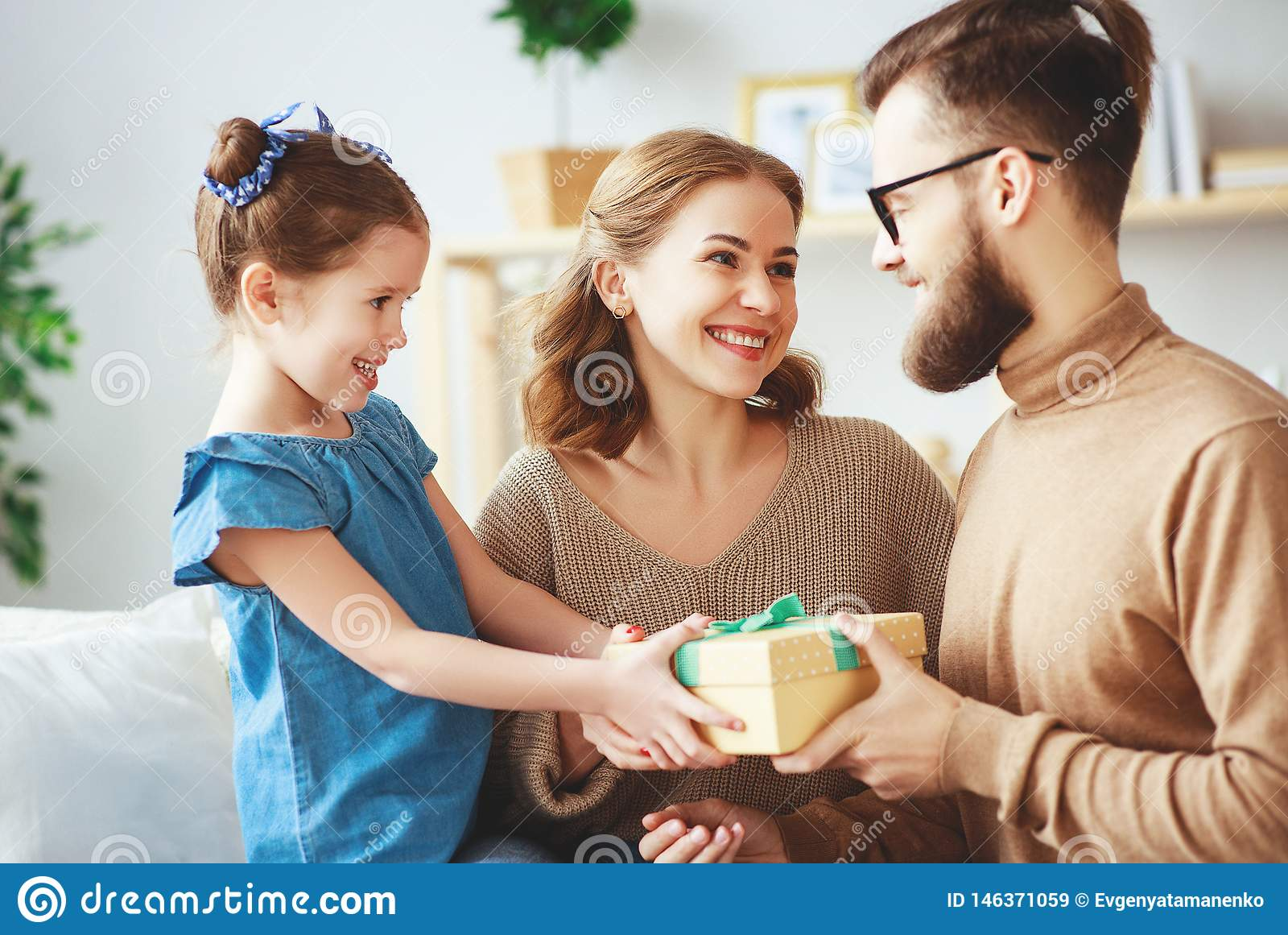 Happy father`s day! family mom and daughter congratulate dad and give gift