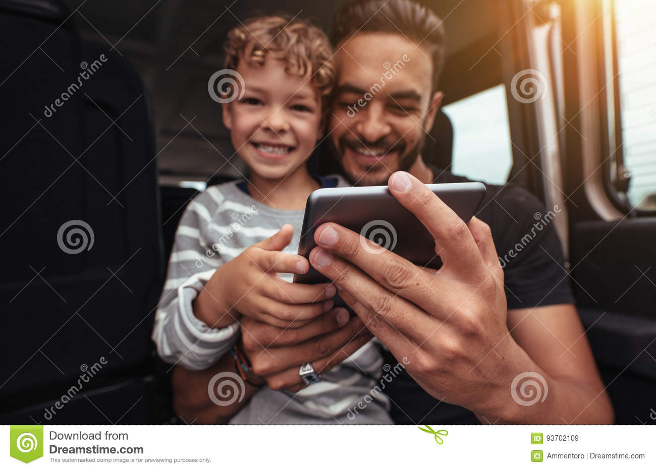 Happy father and son at the back of car with digital tablet