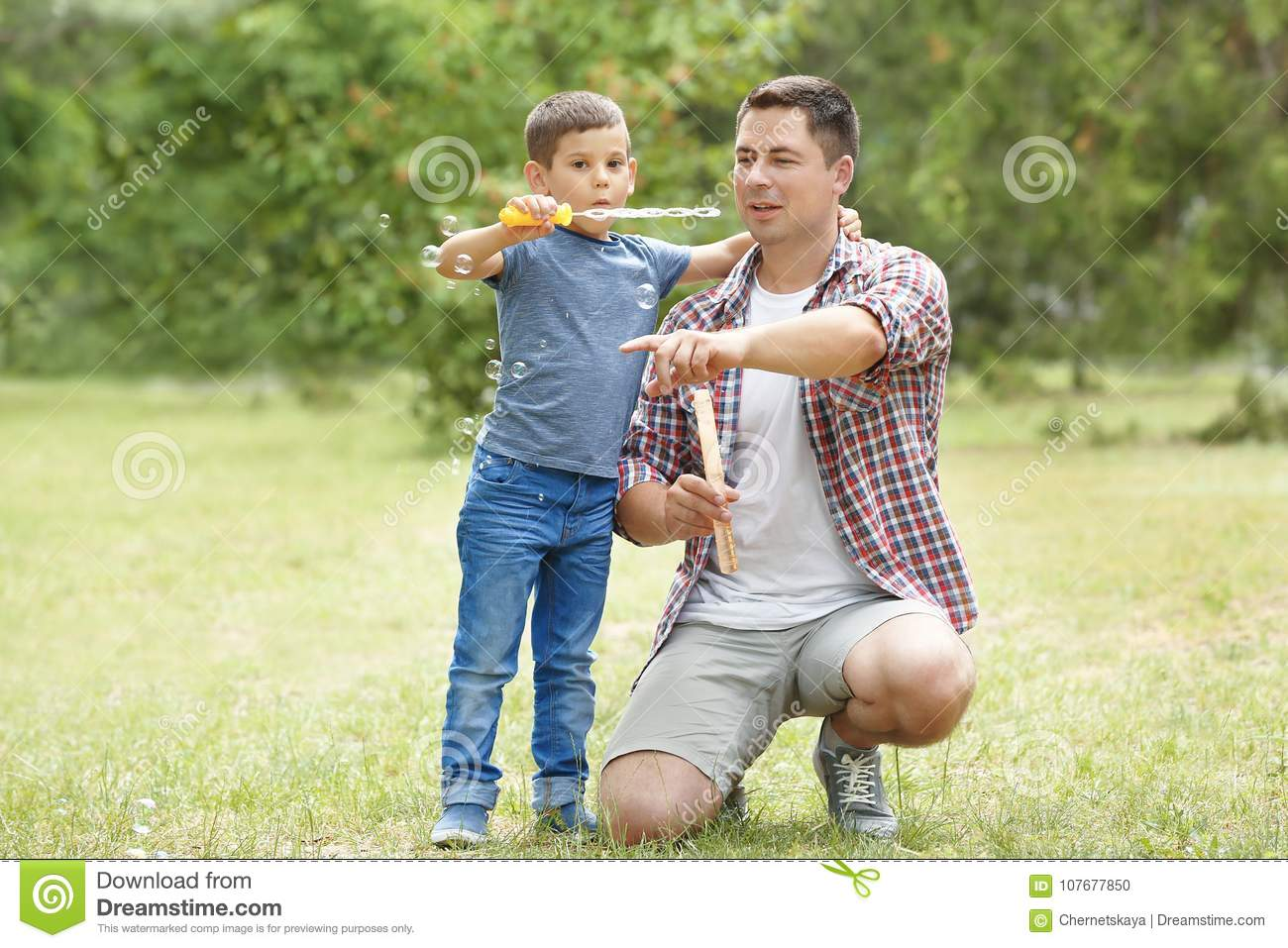 Happy Father And Son Blowing Soap Bubbles Stock Photo