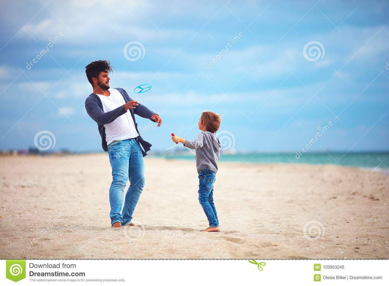 Happy father and son having fun on the beach, playing summer activity games, launching propeller toy in the air