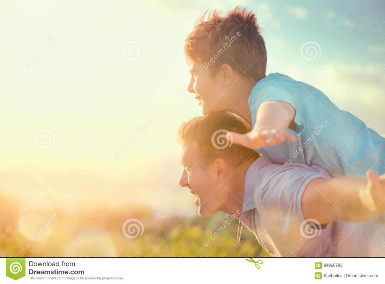 Happy father and son having fun over beautiful sky outdoors