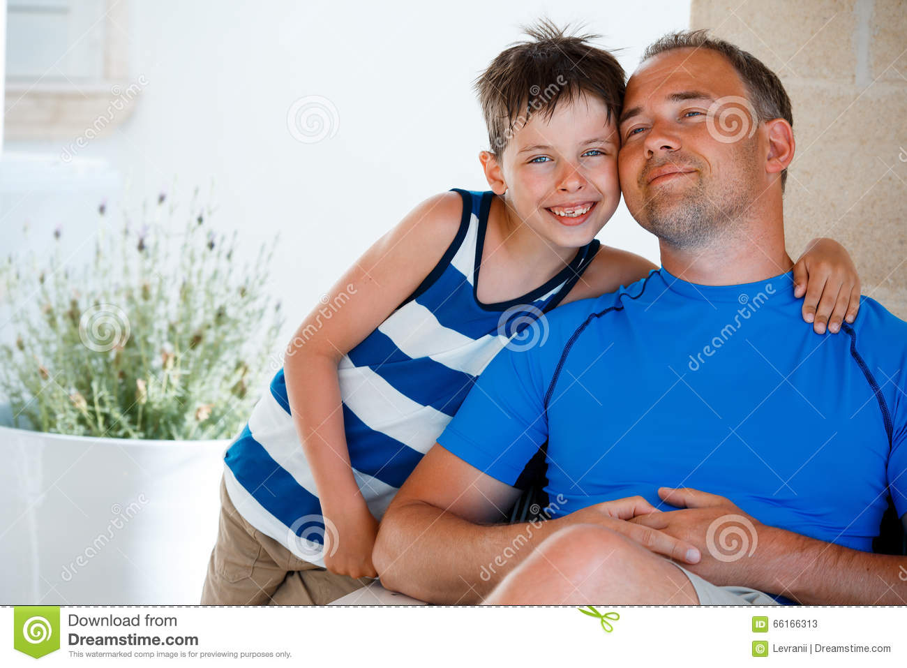 Happy father and son having rest outdoors on beautiful summer day