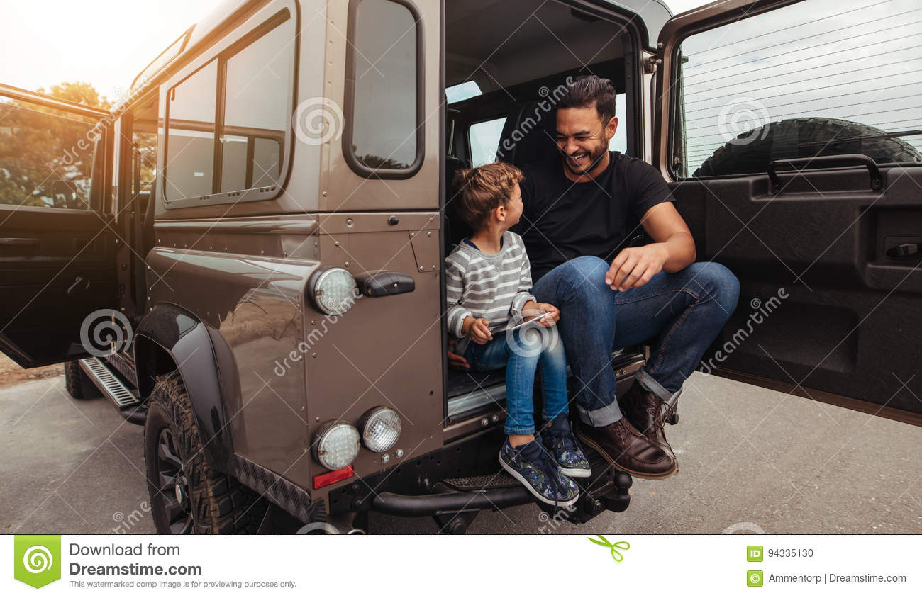 Happy father and son sitting at the back of the car