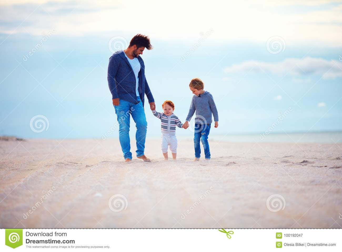 Happy father and sons walking on sandy autumn beach near the sea