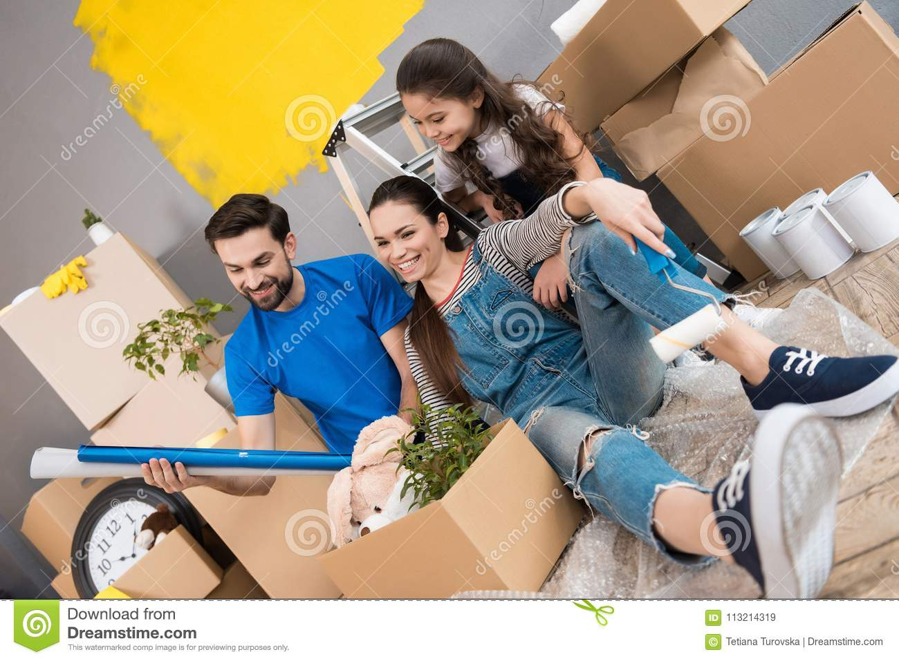 Happy father and wife and daughter sort things out from cardboard boxes in house they moved.