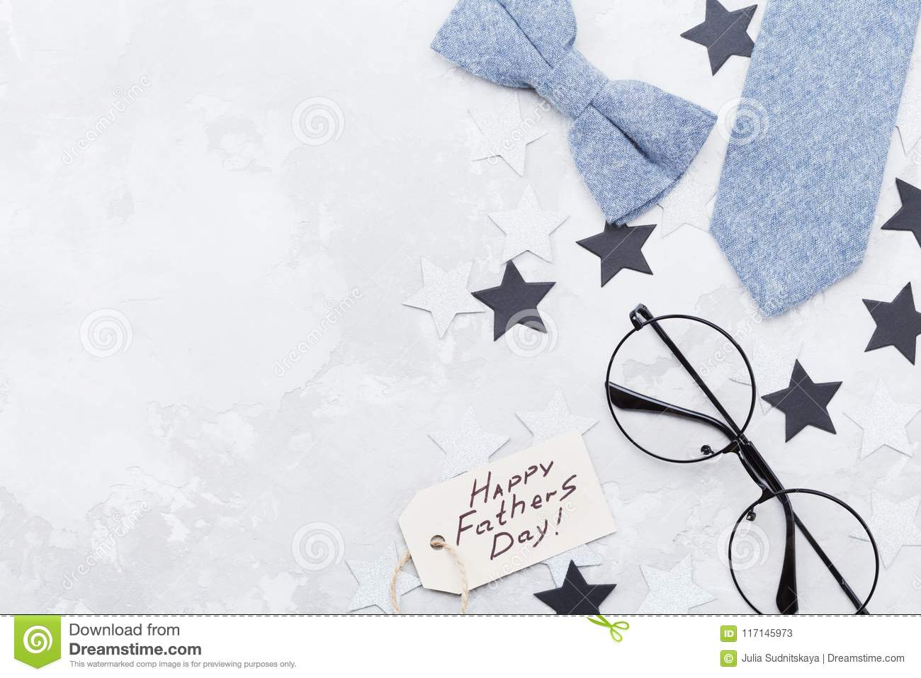 Happy Fathers Day background with greeting tag, glasses, necktie, bowtie and star confetti on table top view. Flat lay.