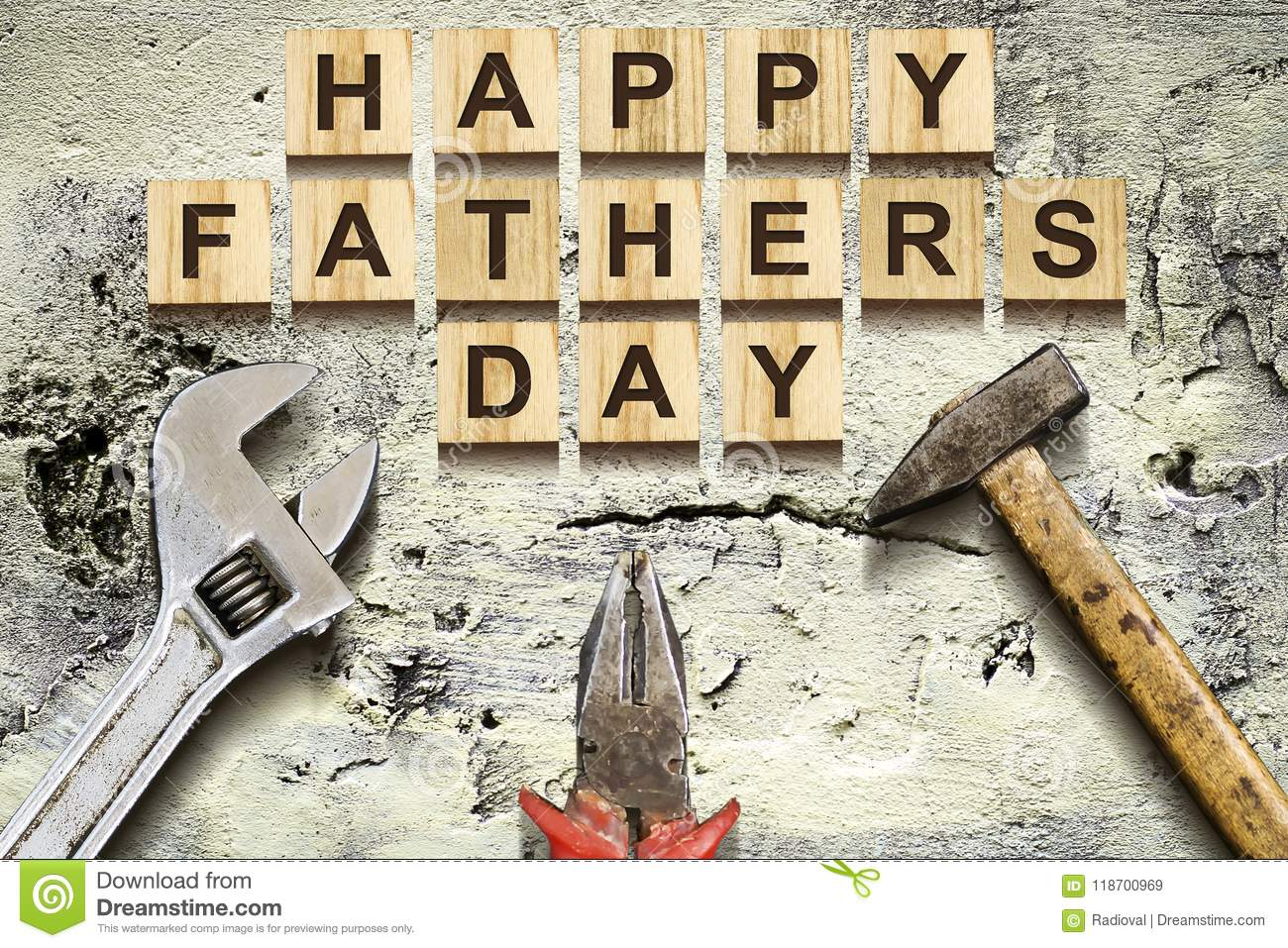 Happy Fathers Day inscription on wooden cubes with working tools on an old vintage concrete wall. Happy Father`s Day Concept. Gre