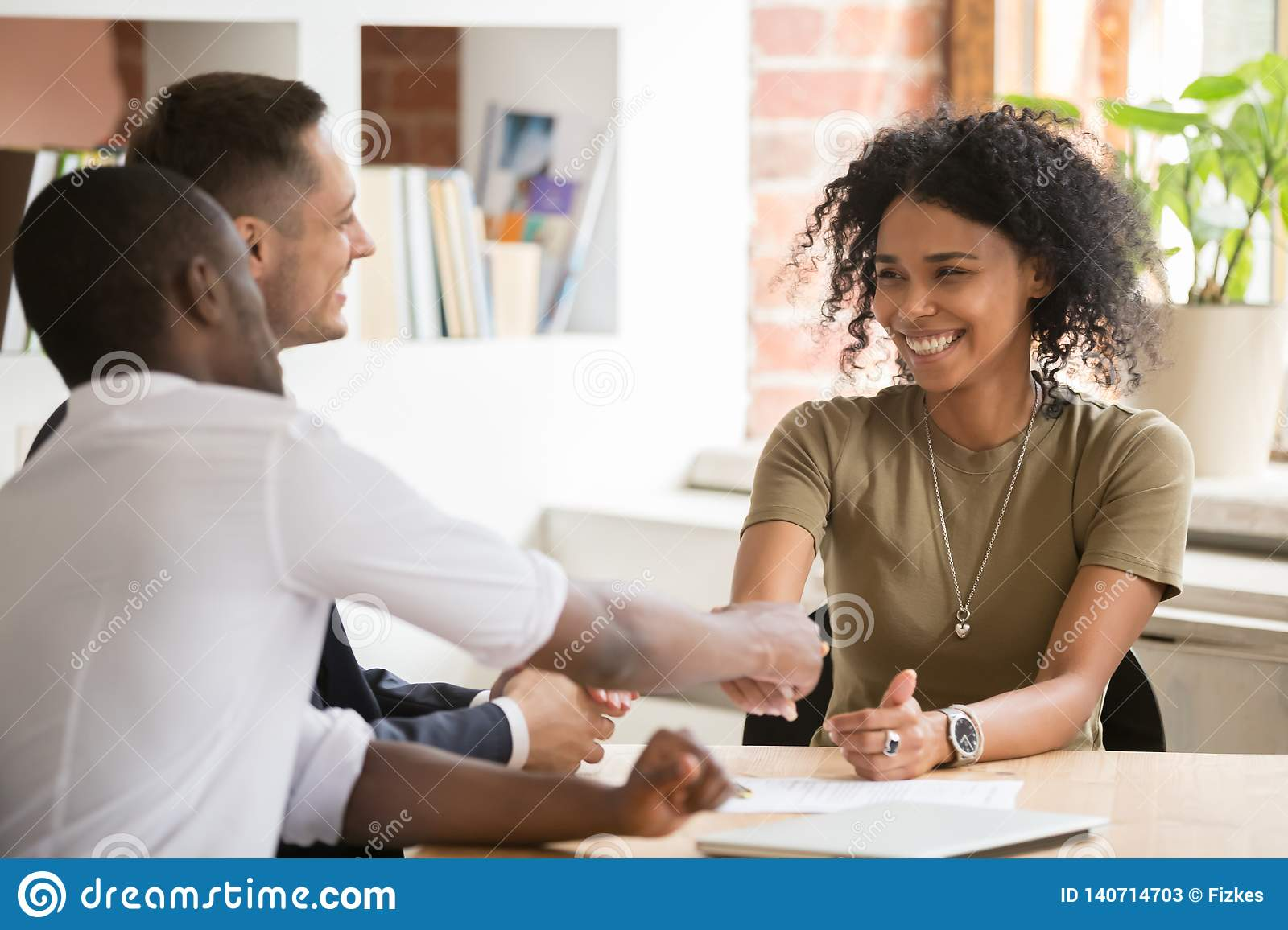 Happy female african vacancy candidate shaking hand of hr manager