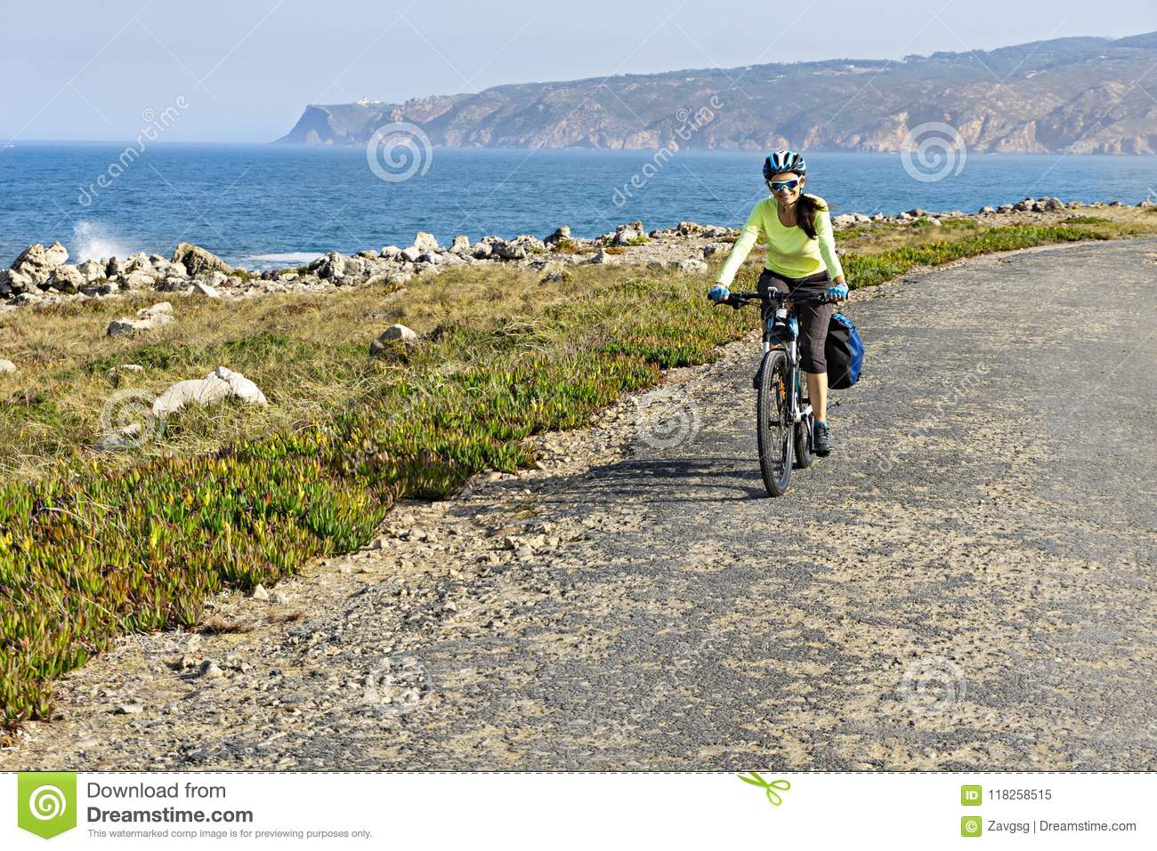 Happy female cyclist rides bicycle on road along ocean shore.