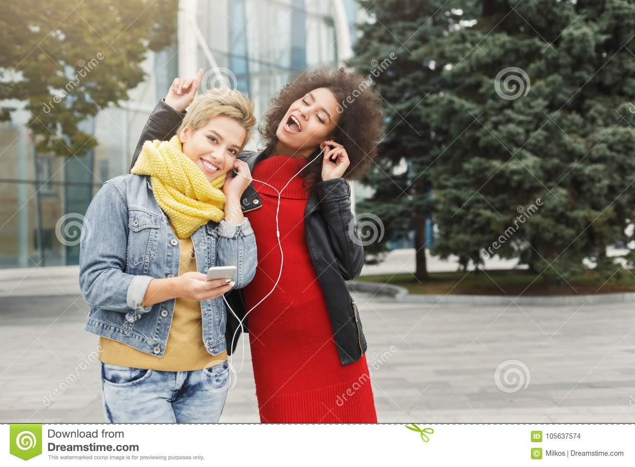 Happy Female Friends Listen To Music Outdoors Stock Photo