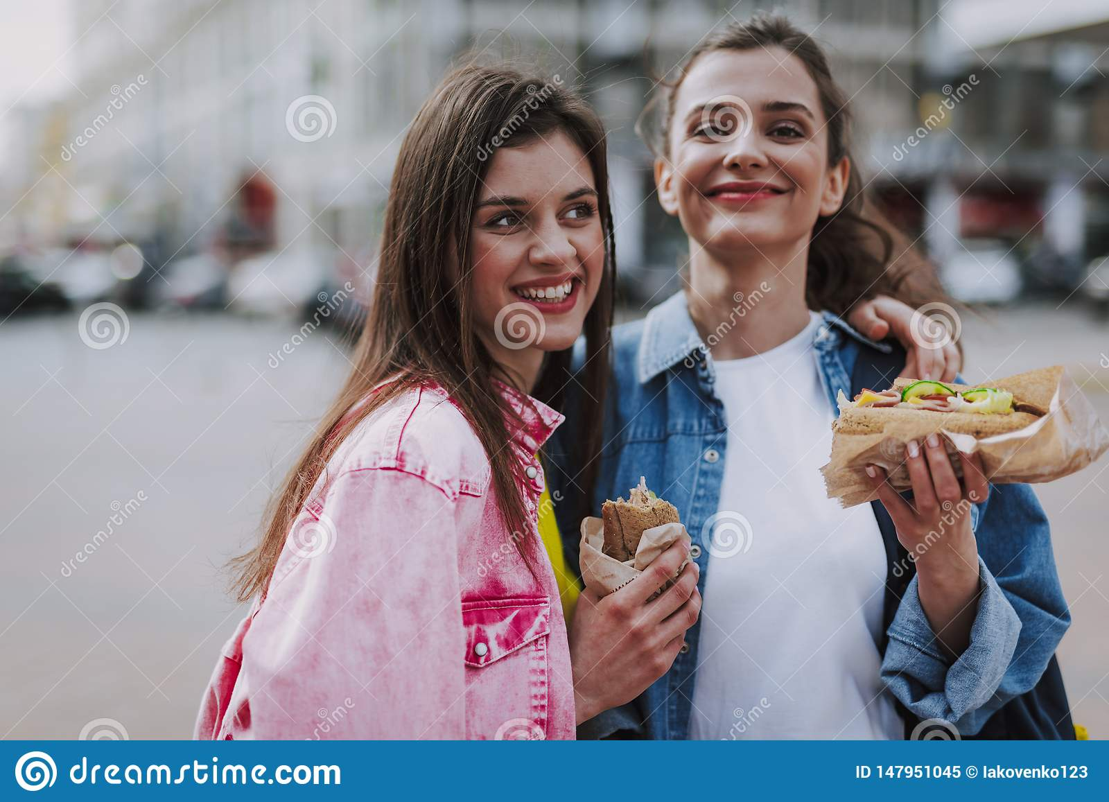 Happy female friends making photo with hot dogs