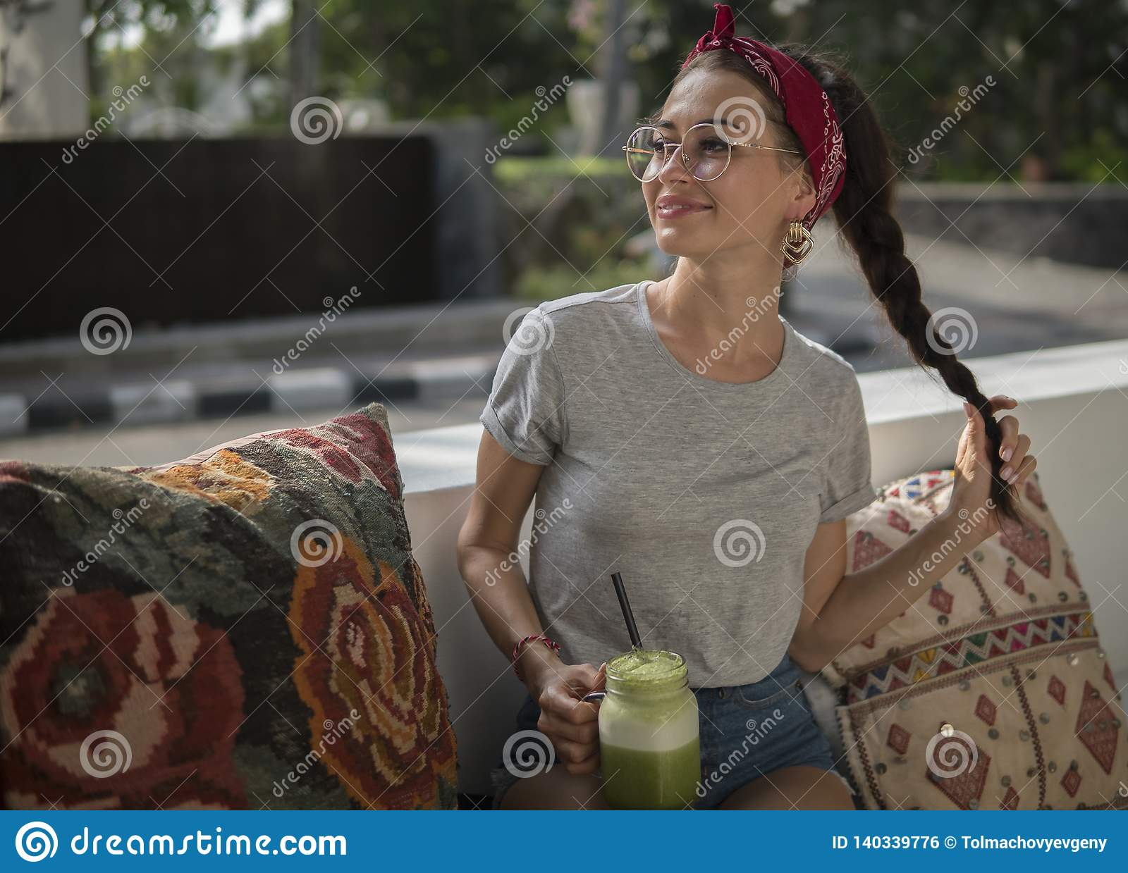 Happy female having rest in the outdoor cafe on bench with cushions, gorgeous adult girl with beautiful smile holding
