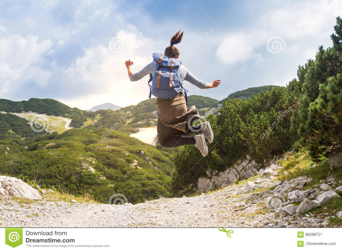 Happy female hiker jumping in mountains on a beautiful sunny day