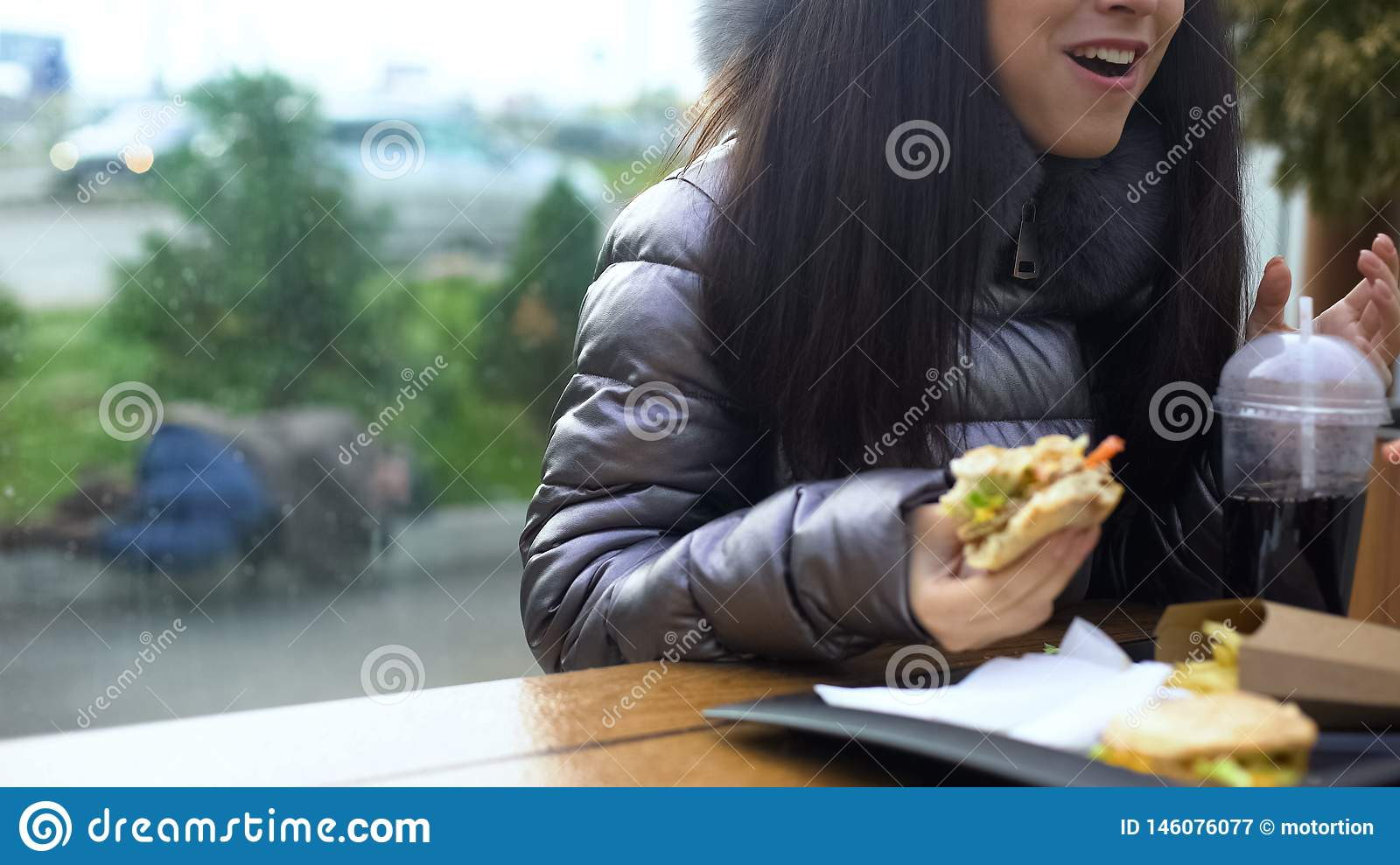 Happy female holding sandwich having dinner cafe, homeless person lying outdoor