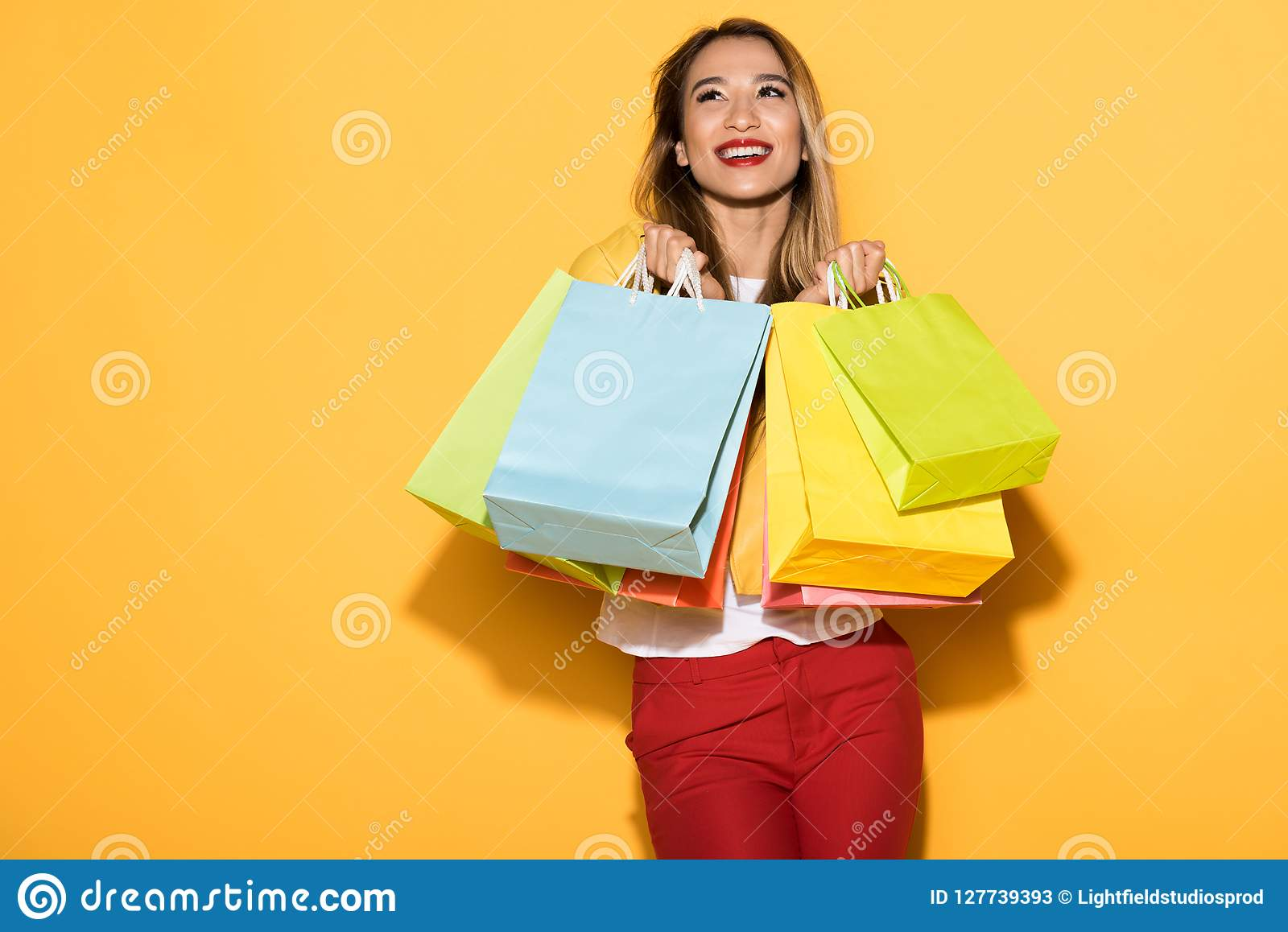 happy female shopper standing with paper bags on yellow