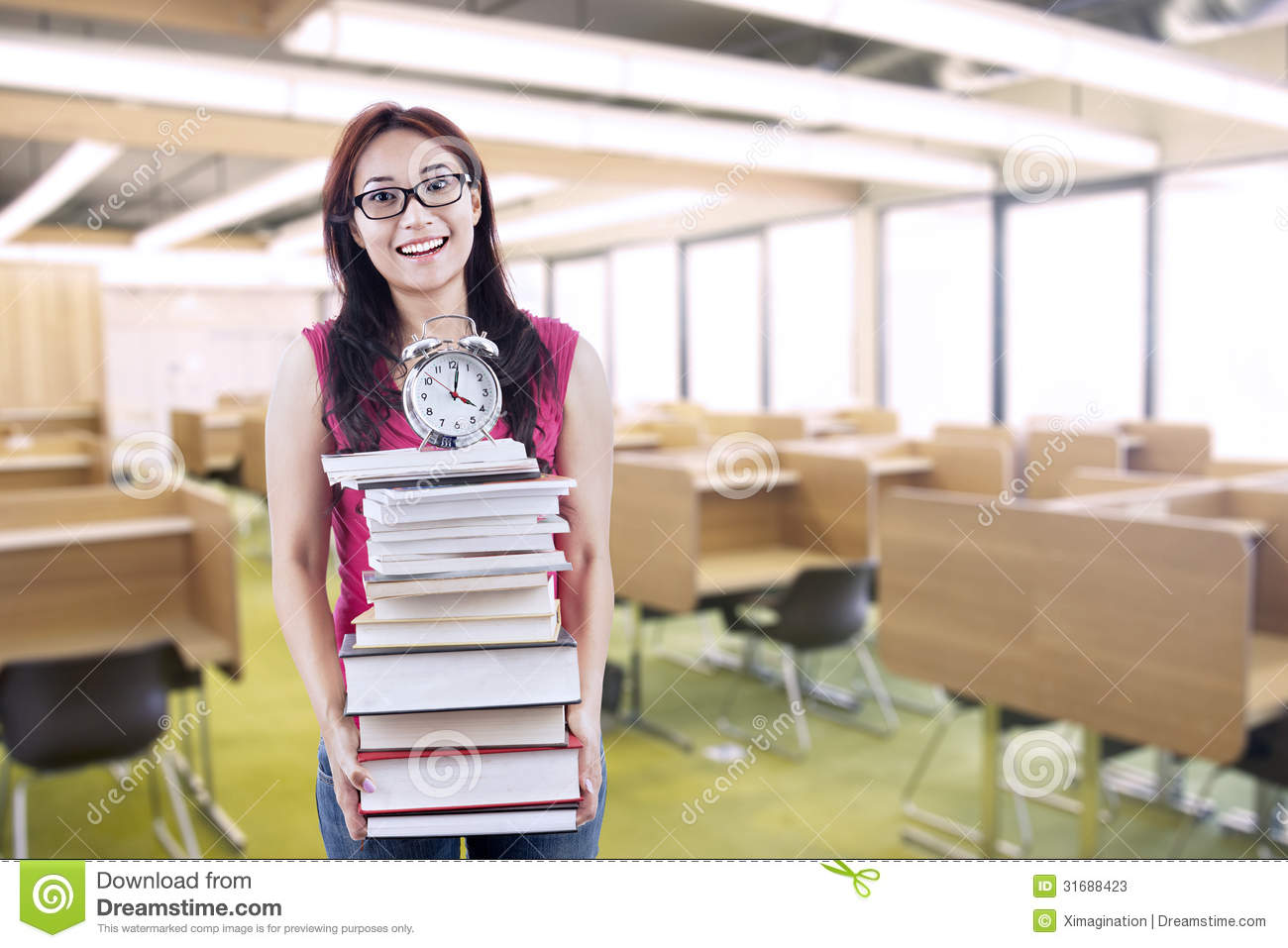Happy Female Student Bring Stack Of Books And Clock Stock