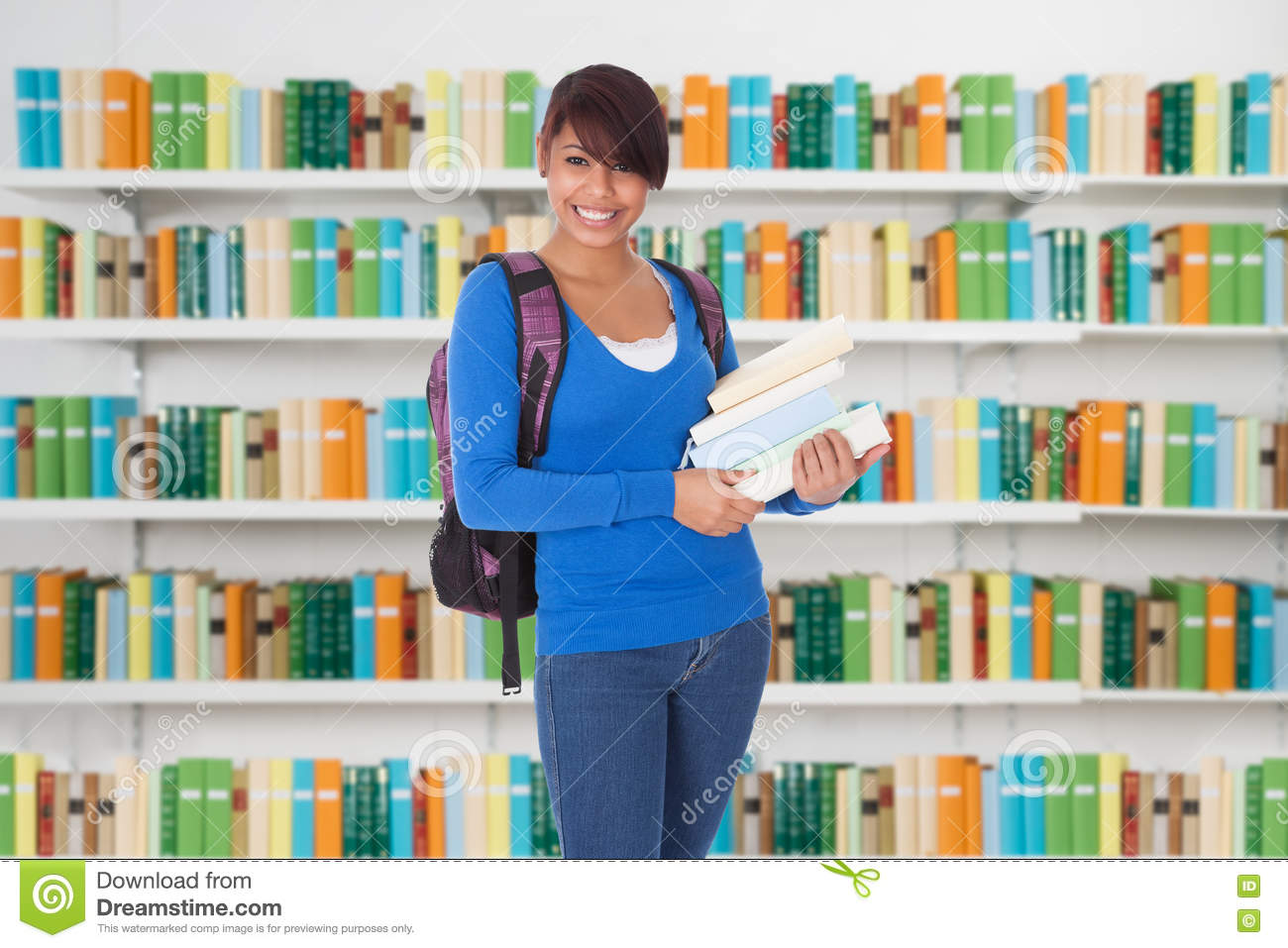 Happy Female University Student Standing In Library