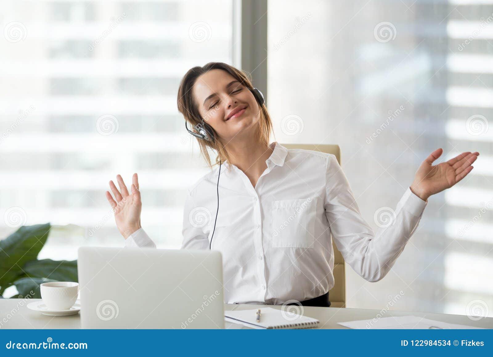 Happy female worker enjoying favorite music at work