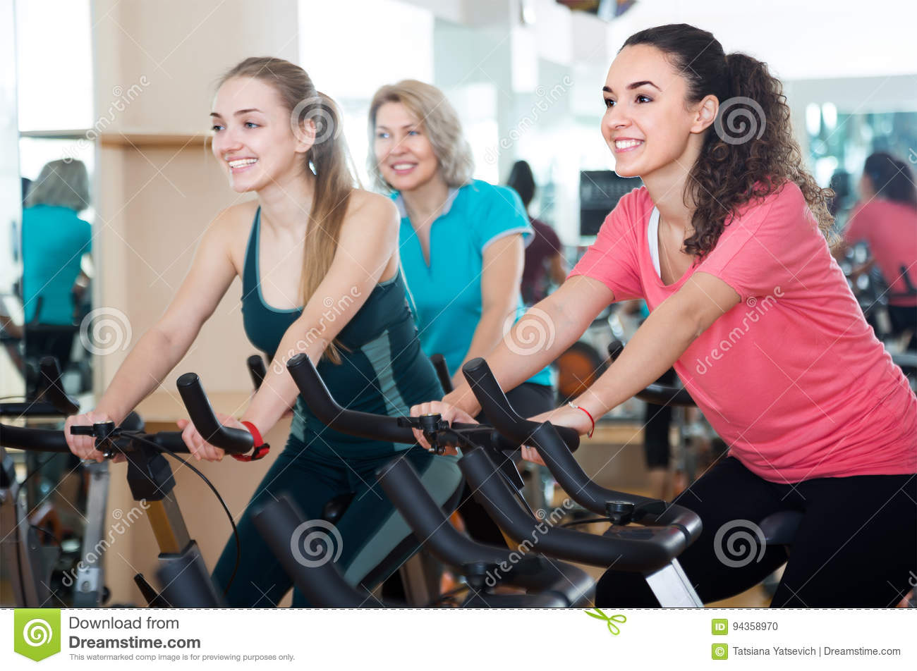 Happy Females Of Different Age Training On Exercise Bikes Stock