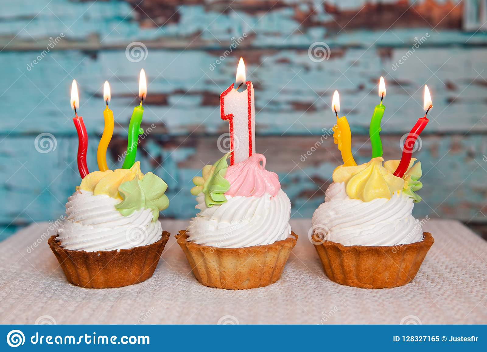 Happy First Birthday Cake And Number One Candle On Blue Background