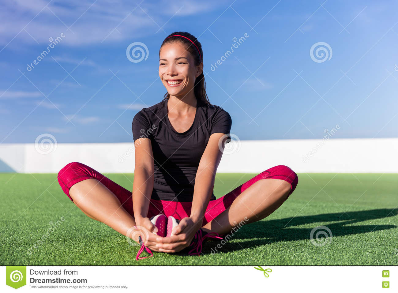 Happy fitness Asian woman stretching legs in park