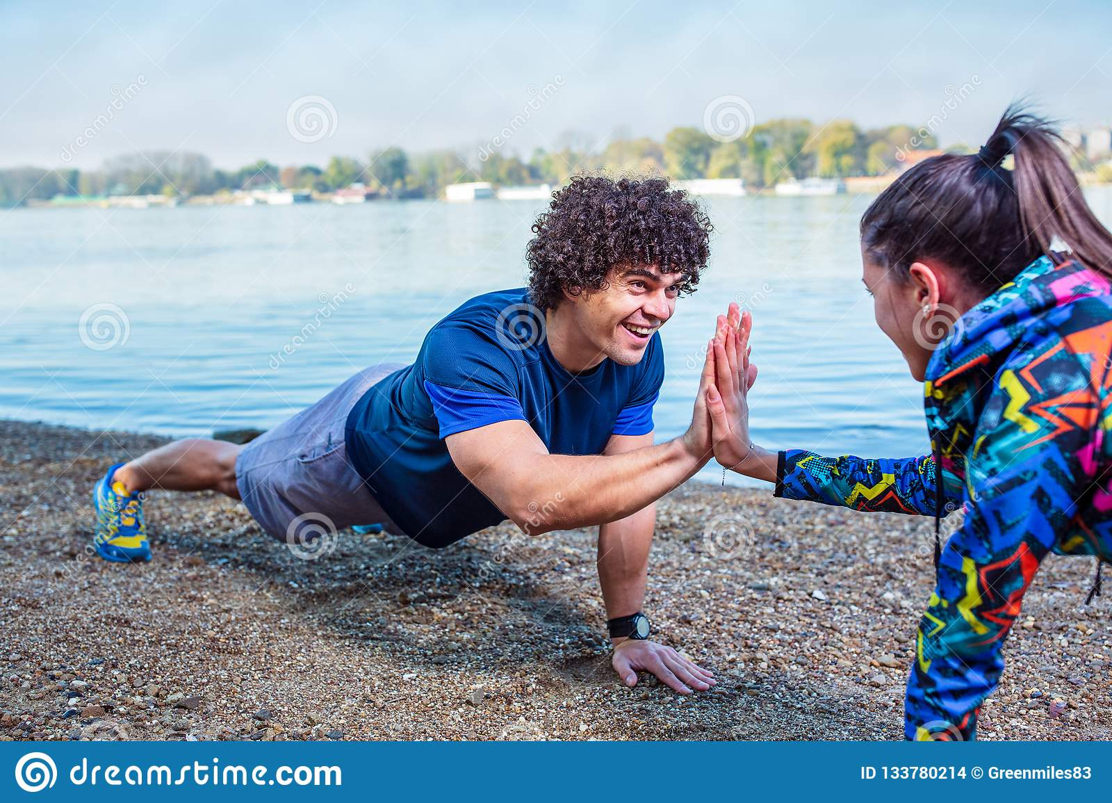 Happy fitness couple giving high five to each other while doing