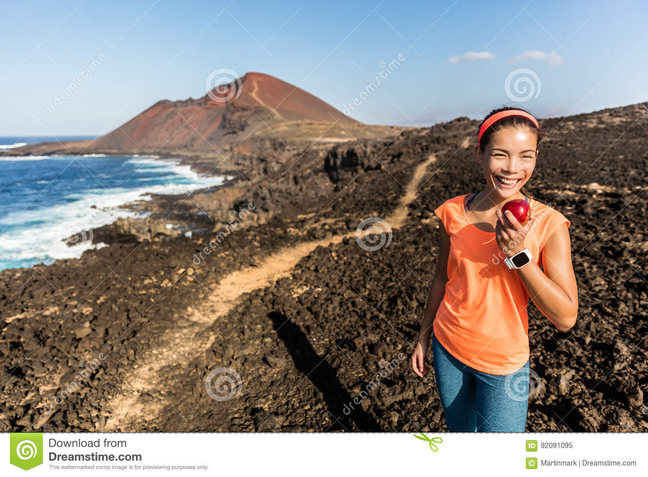 Happy fitness woman on hiking trail eating apple