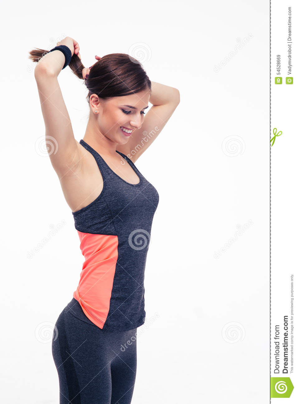 Happy fitness woman holding her hair in ponytail