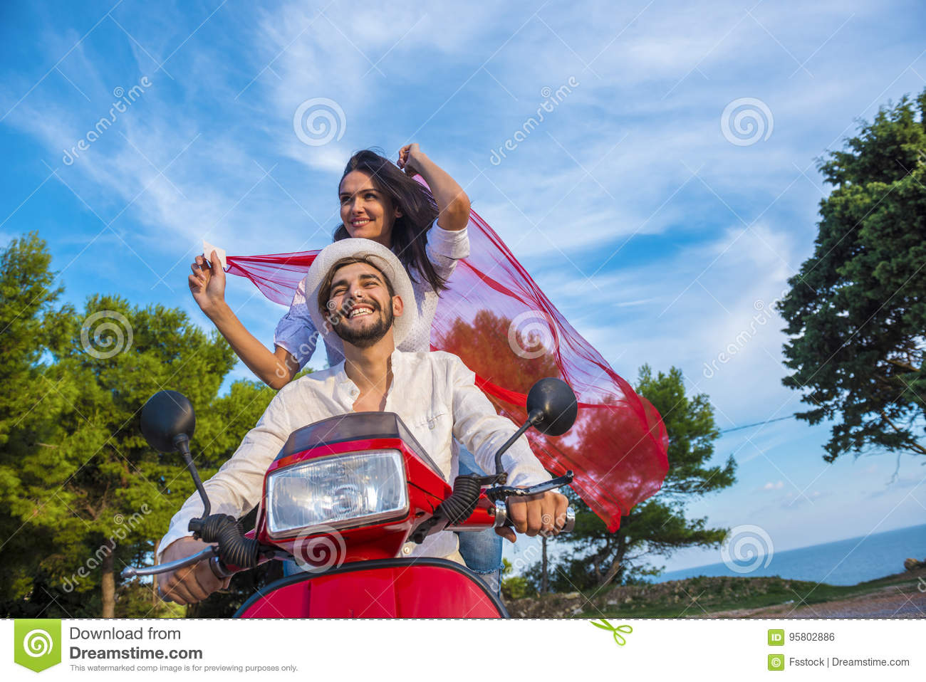 Happy free freedom couple driving scooter excited on summer holidays vacation.