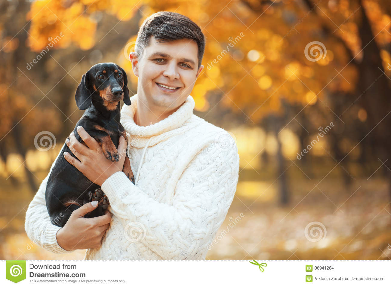 Happy free time with beloved dog! Handsome young man staying in autumn park smiling and holding cute puppy dachshund.