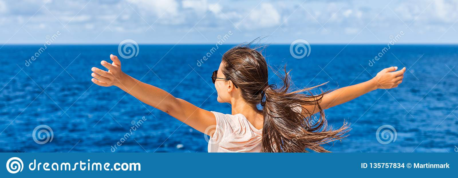Happy freedom woman with open arms looking at sea