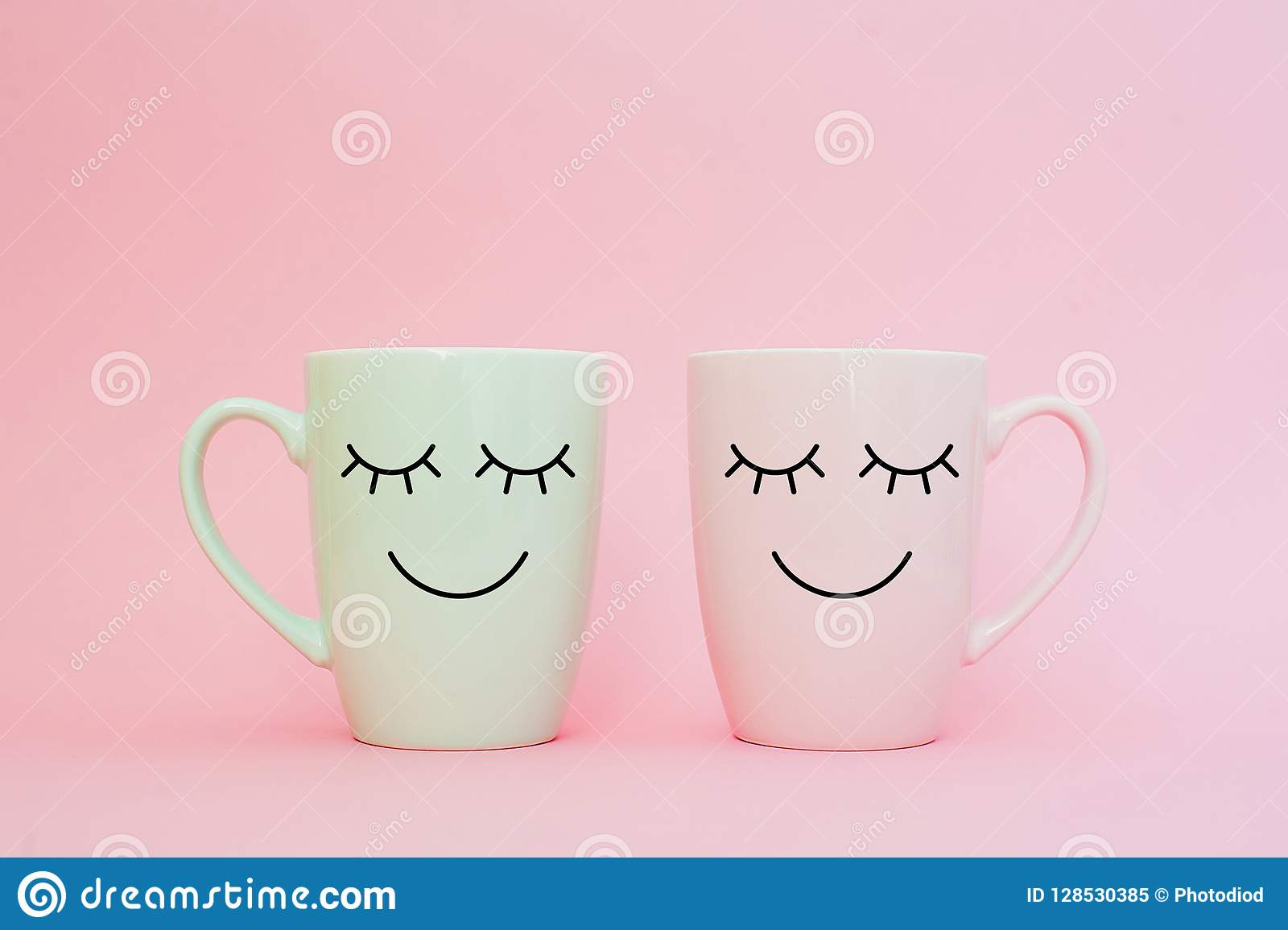 Happy friday word. Two cups of coffee stand together to be heart shape on pink background with smile face on cup.