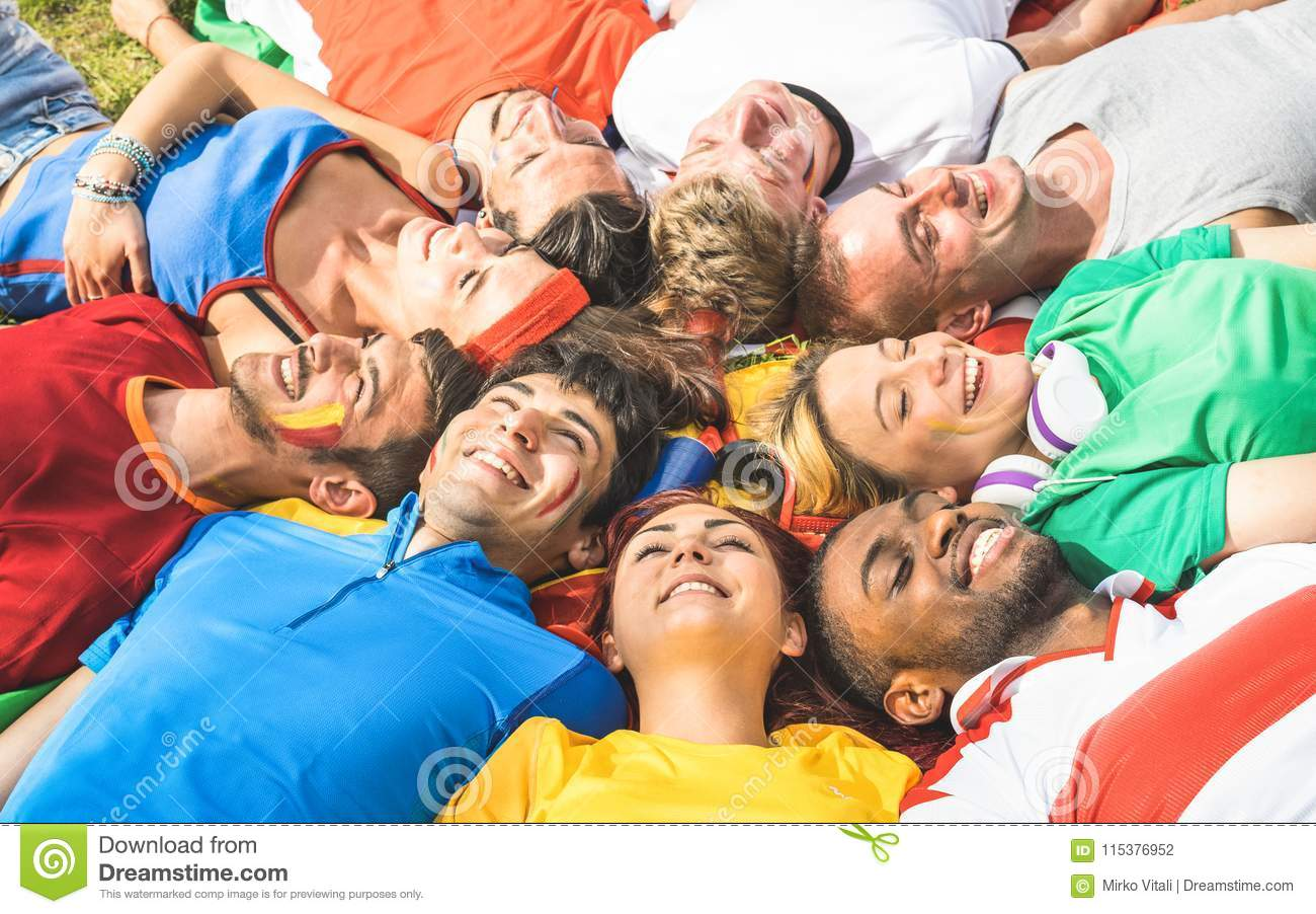 Happy friend group lying on meadow after world soccer event - Fr