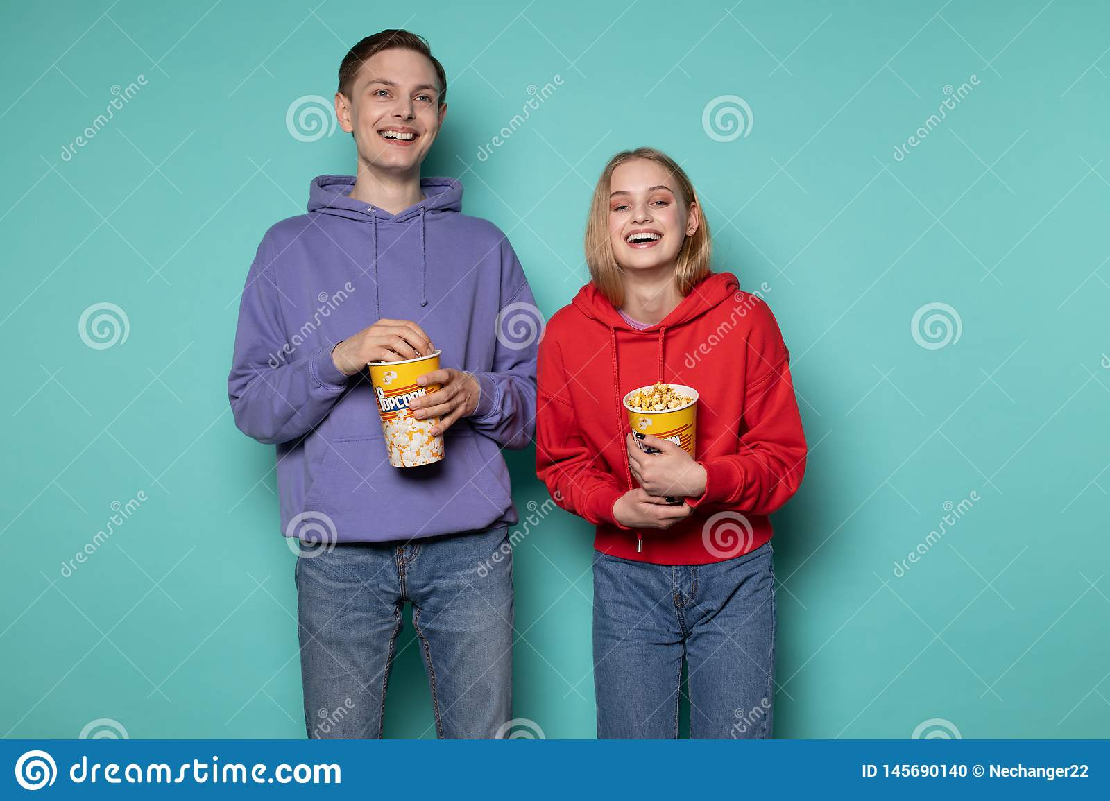 Happy friends, beautiful blonde girl and guy in purple hoodie watching a comedy movie with popcorn in hands