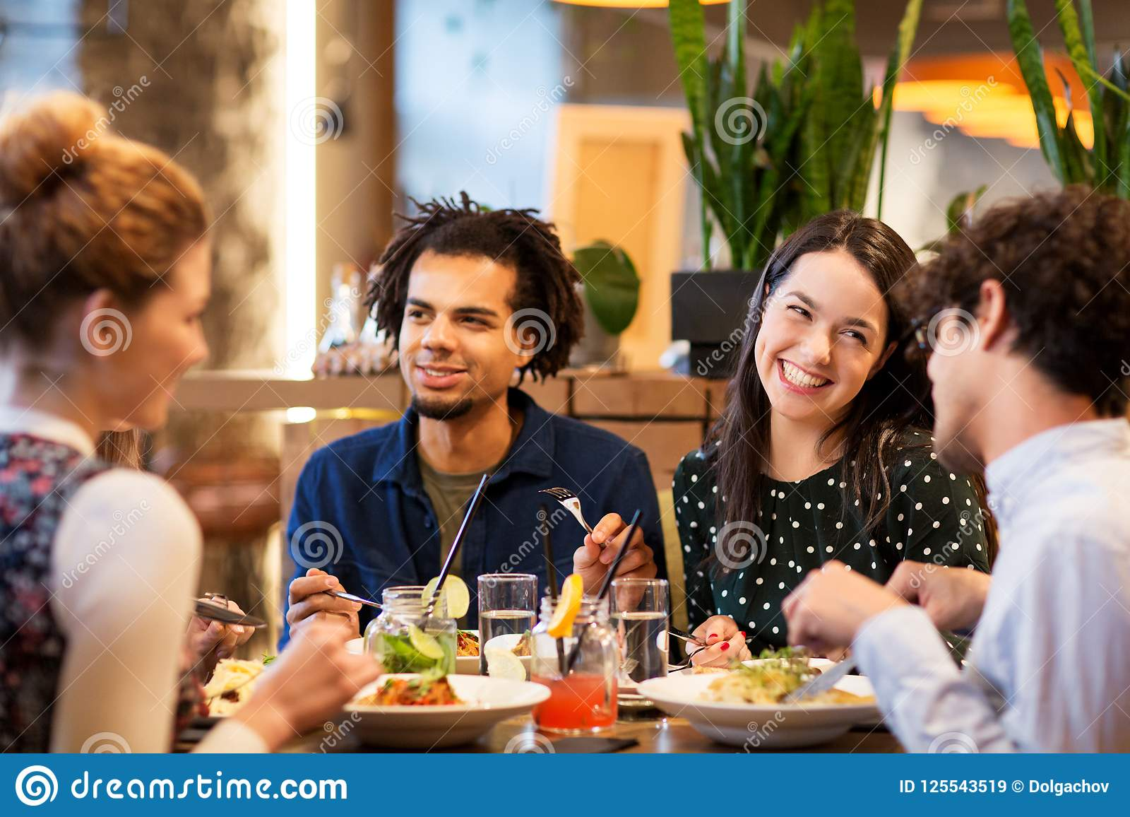 Happy friends eating at restaurant