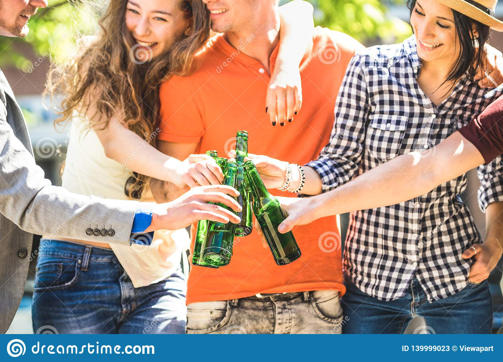 Happy friends group drinking and toasting bottled beer on sunny day outdoors - Friendship concept with young people millennials