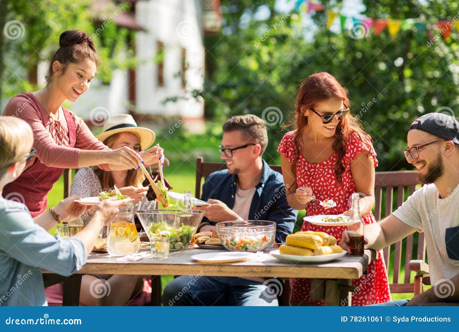Happy Friends Having Dinner At Summer Garden Party Stock