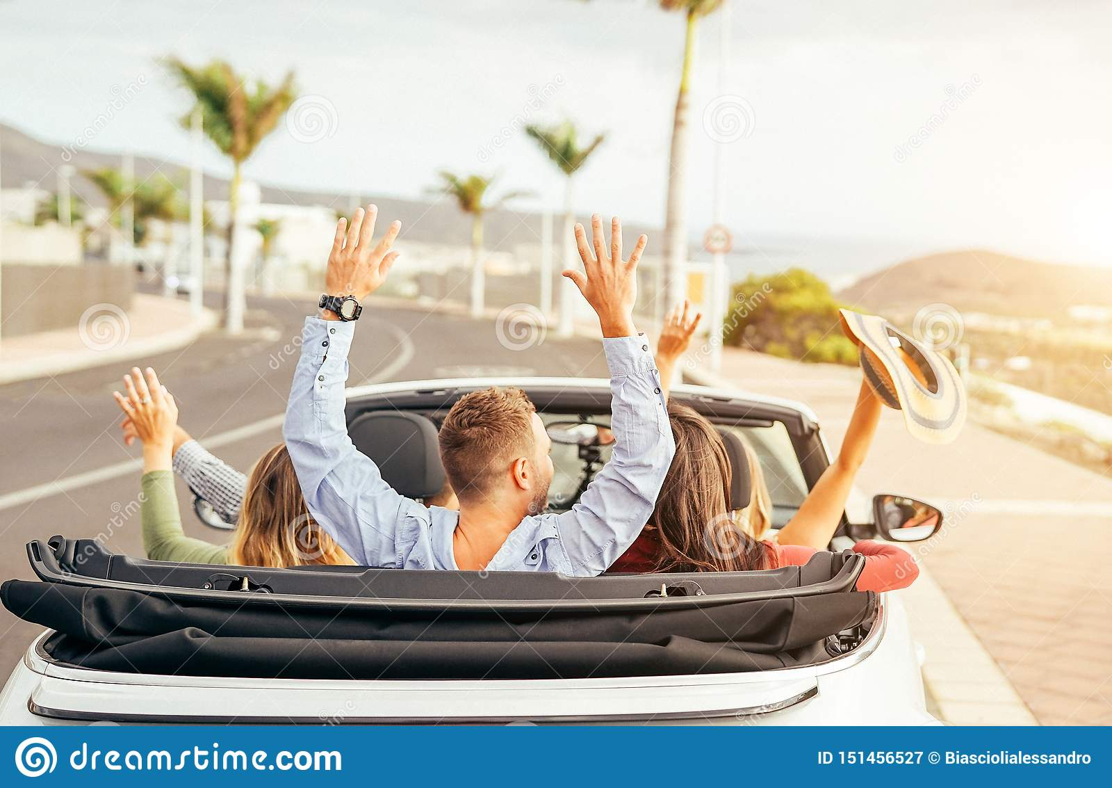 Happy friends having fun in convertible car at sunset in vacation - Young people making party and dancing in a cabrio auto
