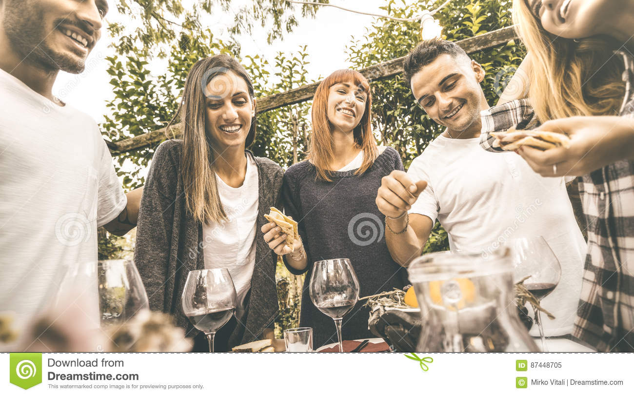 Happy Friends Having Fun Drinking Red Wine Eating At Garden Party