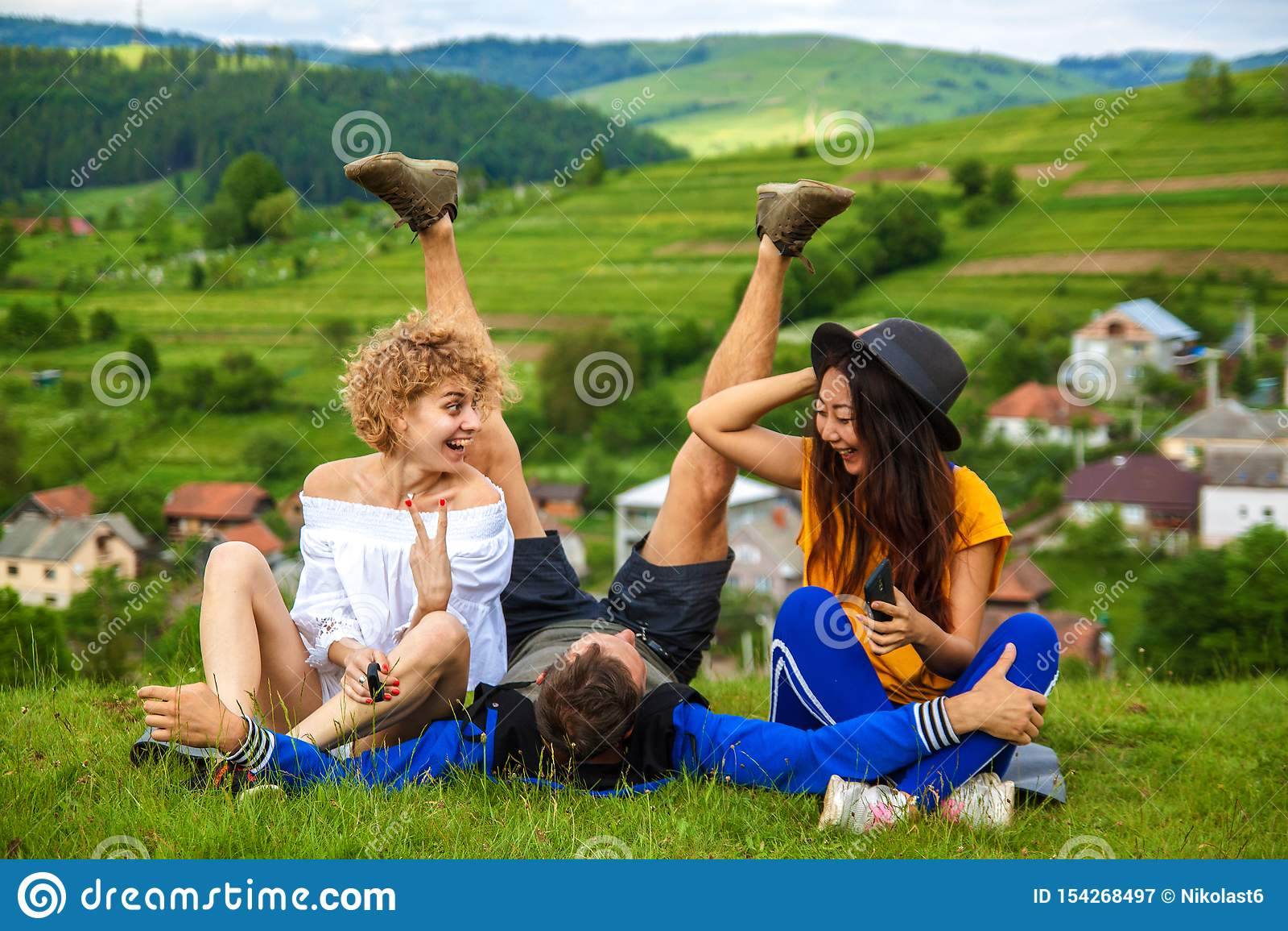 Happy friends having fun on the hill enjoying recreation and talking,horizontal.