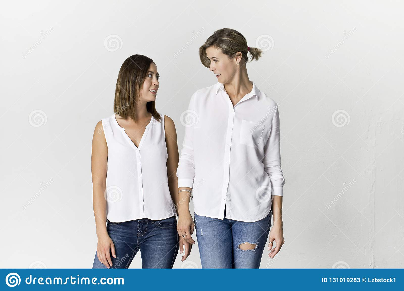 Beautiful attractive funny relaxed carefree girls are greeting in white shirt and jeans on white background