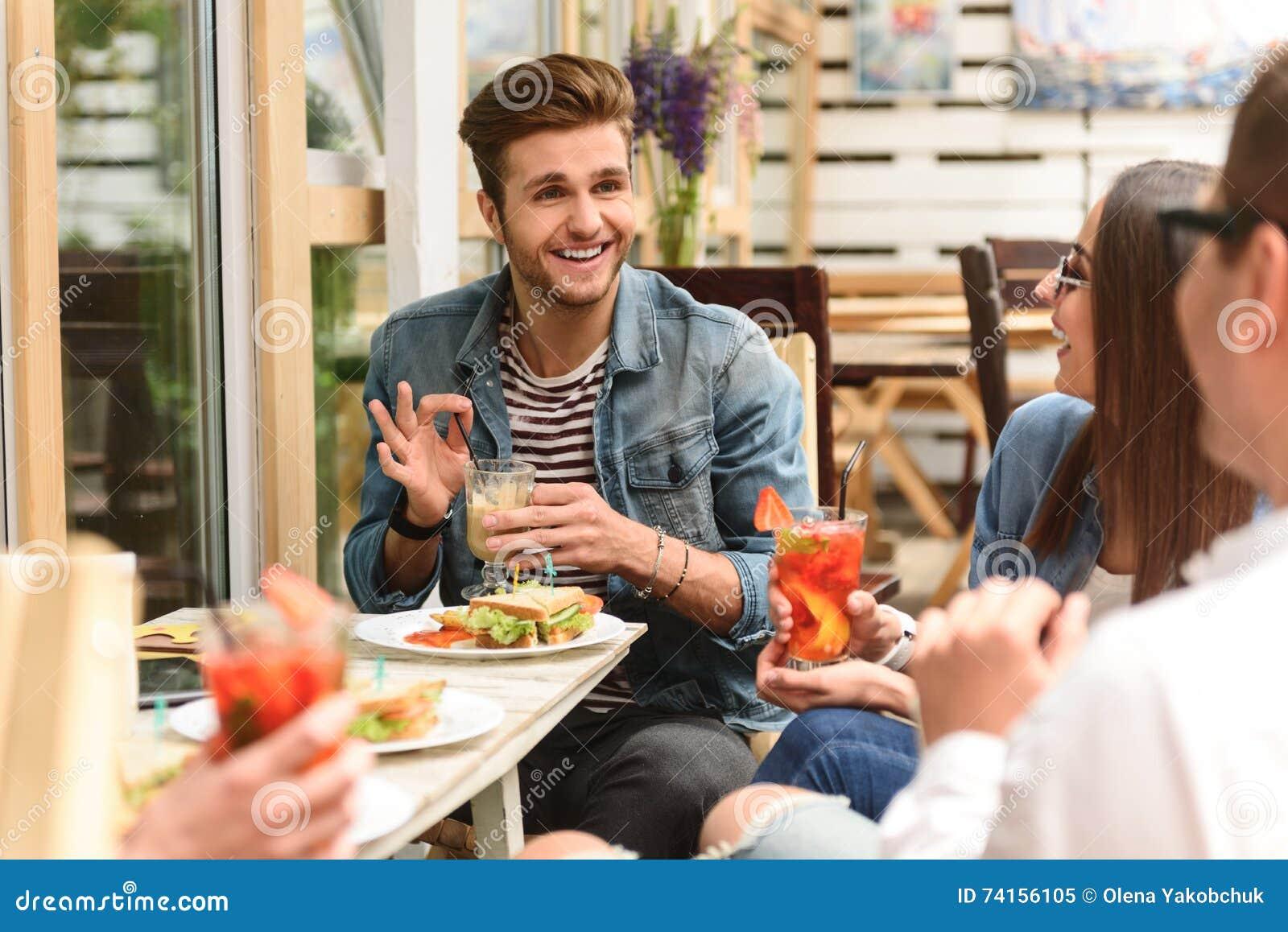 Happy friends having lunch in cafe