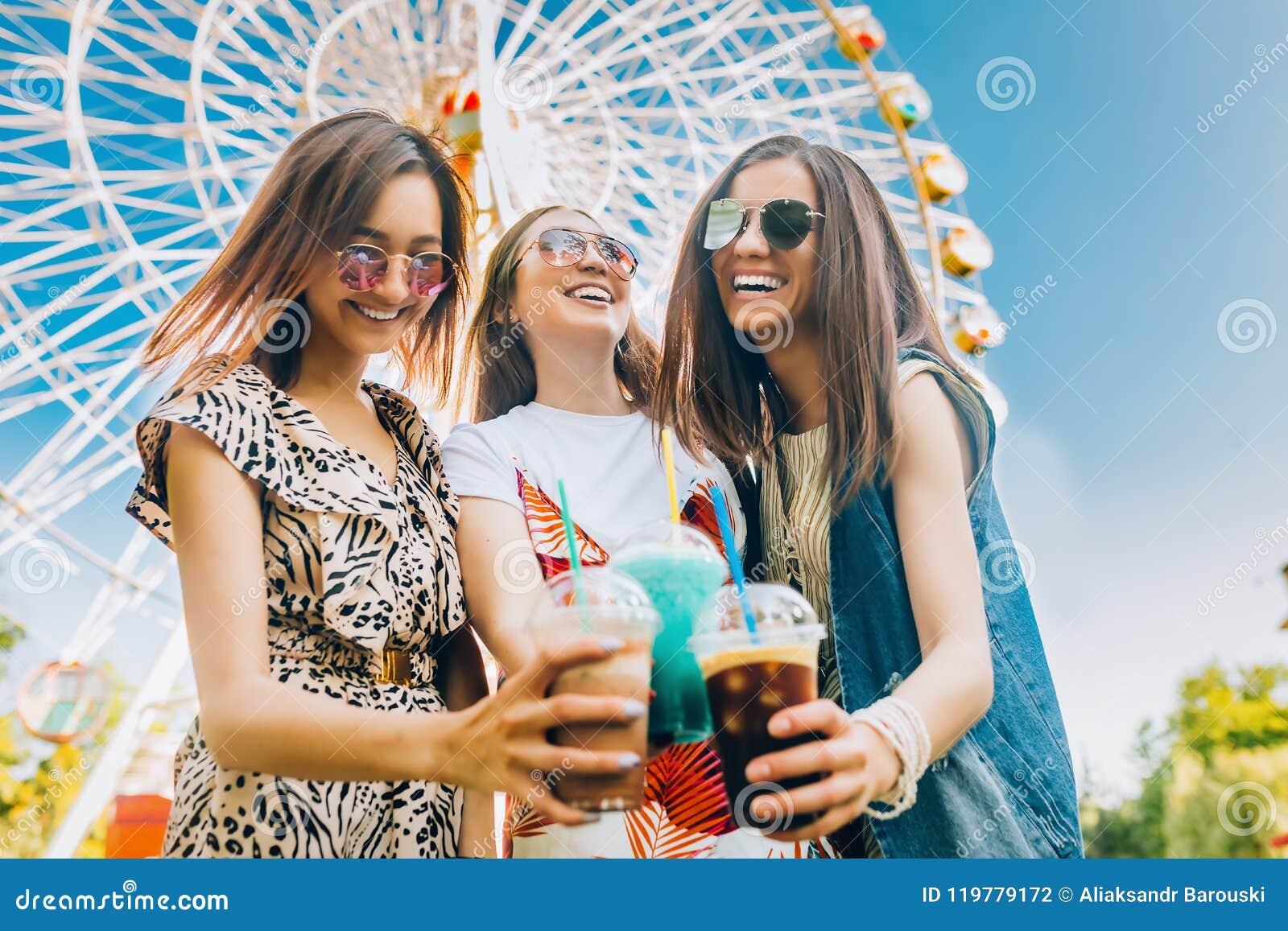 Summer lifestyle portrait multiracial women enjoy nice day, holding glasses of milkshakes. Happy friends inin front of