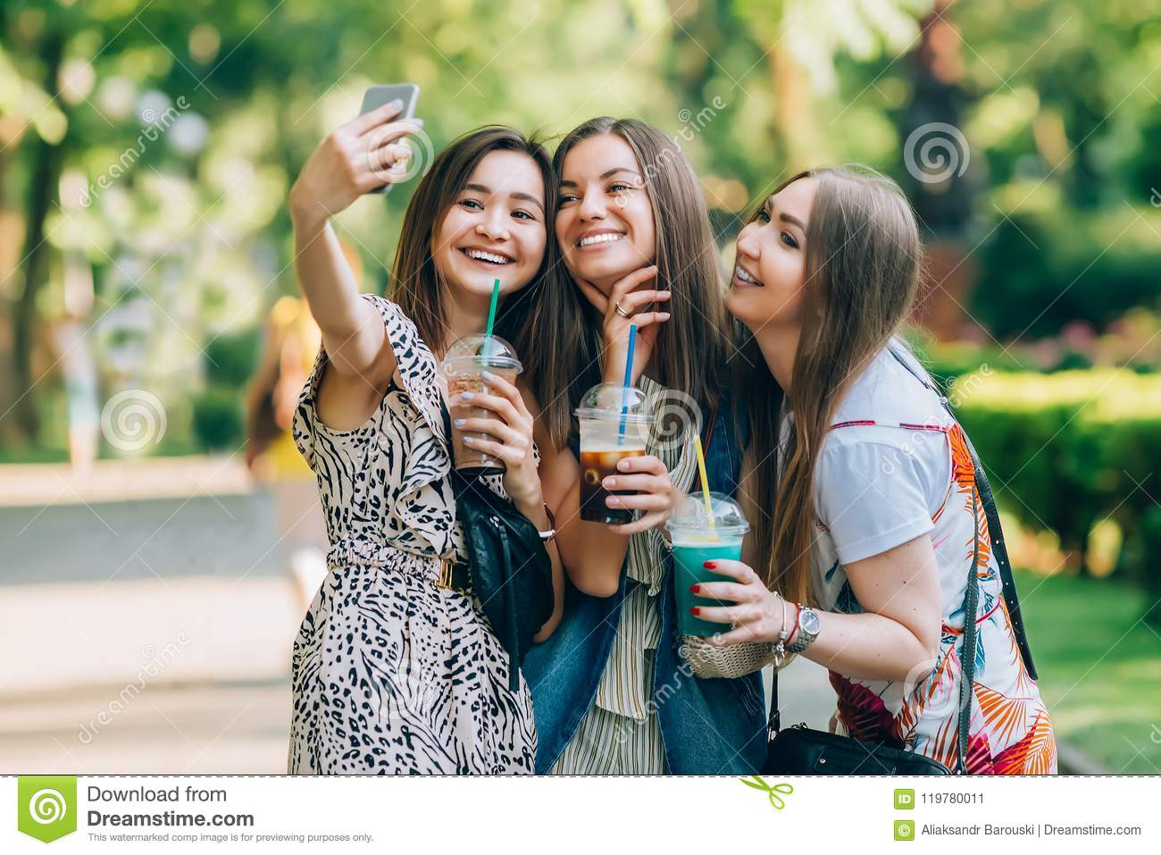Happy friends in the park on a sunny day . Summer lifestyle portrait of three multiracial women enjoy nice day, holding