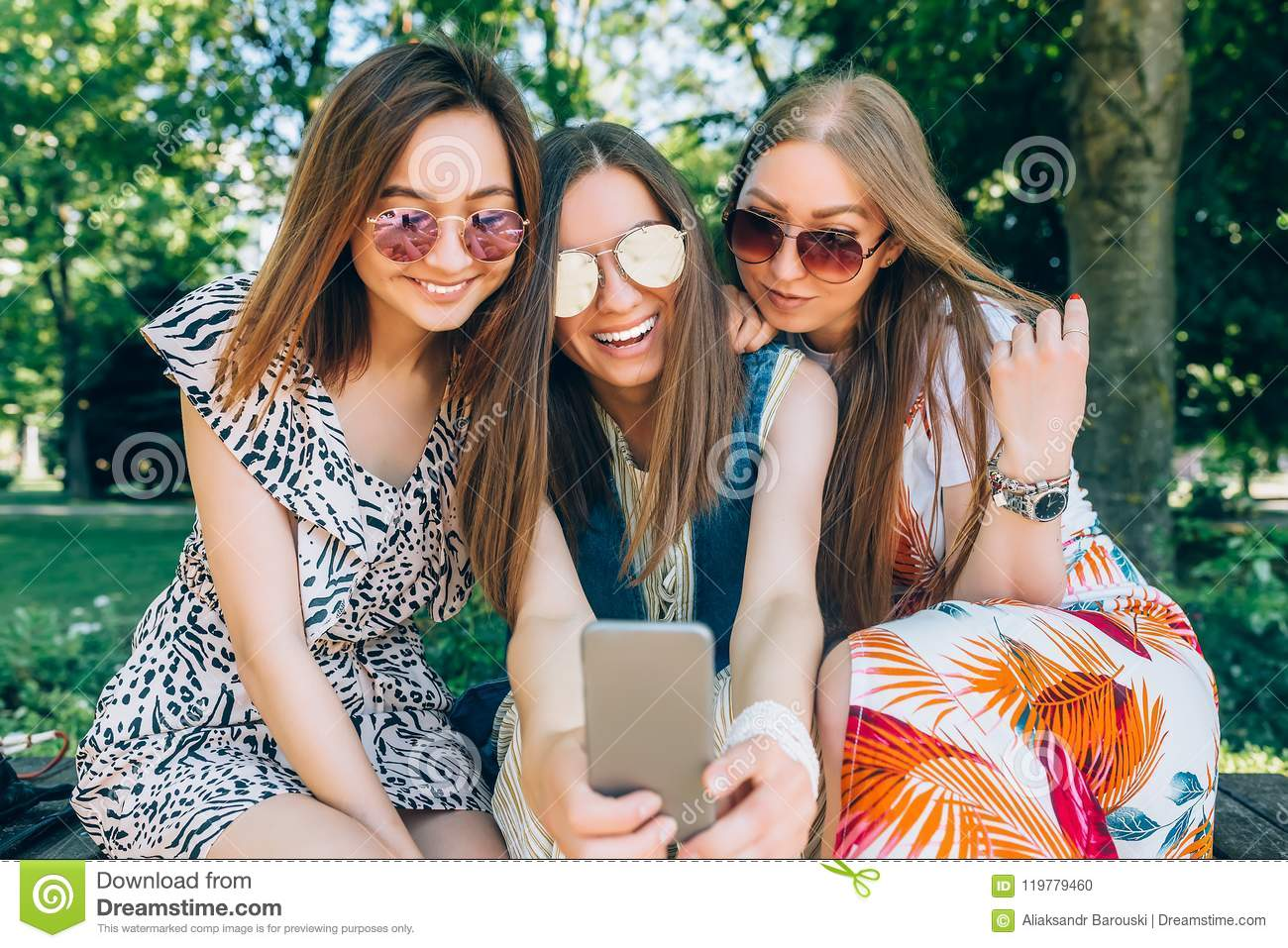Happy friends in the park on a sunny day . Summer lifestyle portrait of three multiracial women enjoy nice day, wearing